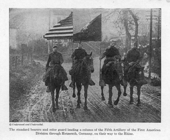 The standard bearers and color guard leading a column of the Fifth Artillery of the First American Division through Hetzerath, Germany, on their way to the Rhine.